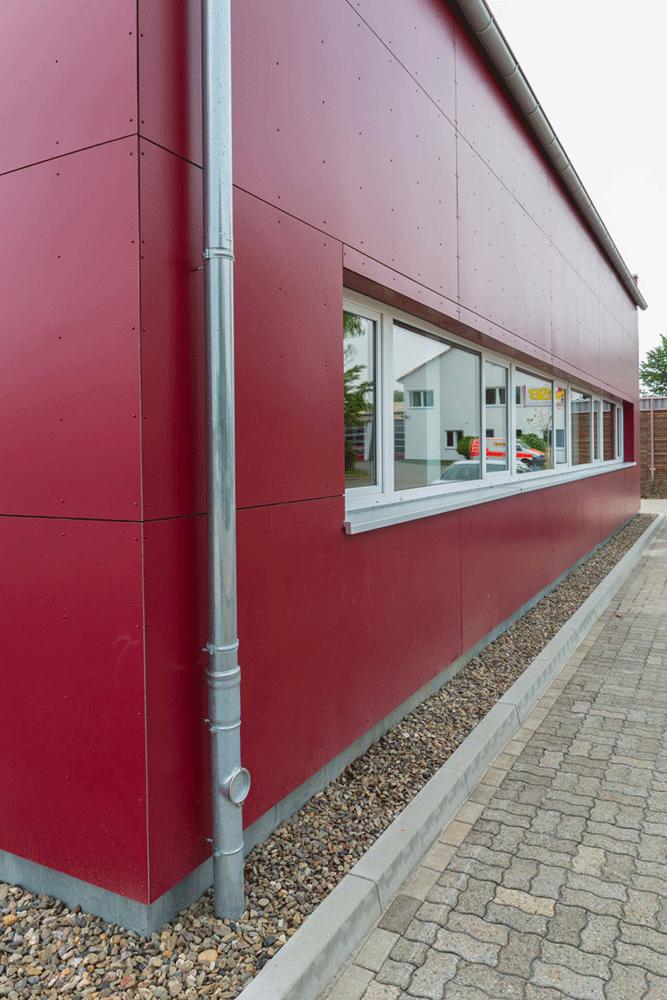 Metalldachrinne an einer roten Fassade
