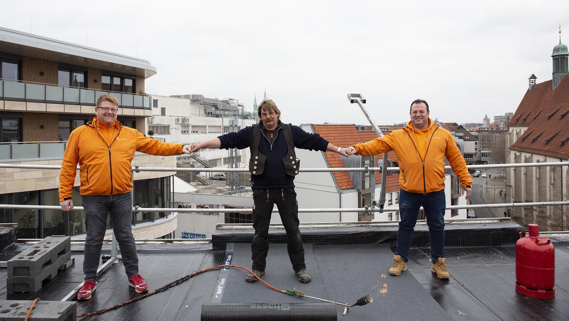 Dachdecker Frank Bauer (M.) mit Dachdeckermeister Peter (l.) und Dirk Marske (r.)